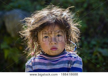 HIMALAYAS ANNAPURNA REGION NEPAL - OCTOBER 14 2016 : Portrait nepalese child on the street in Himalayan village Nepal