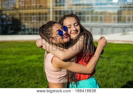 Two girl friends with zizi cornrows dreadlocks hugging each other. Happy moment. Pure emotions