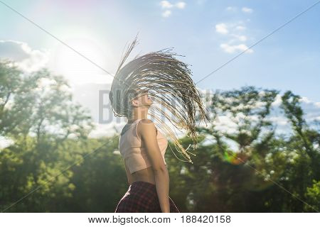 Cheerful girl with zizi cornrows dreadlocks with hair up into air dancing in the sunset on green grass of lawn