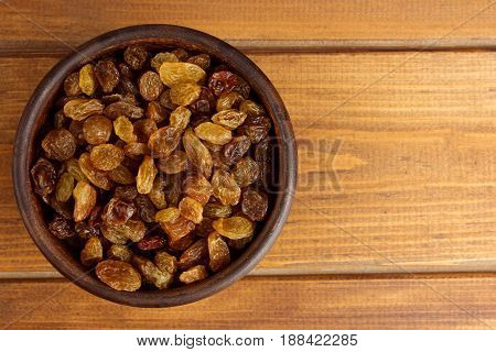 Raisins in bowl over wooden background, tasty, natural