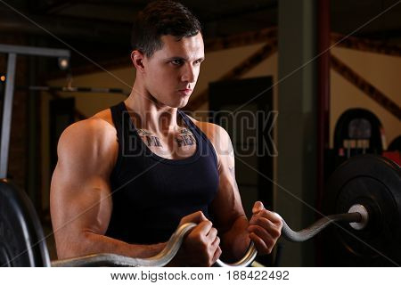 Sporty young man work out biceps. Modern athletic trend health care heavy work calorie burn diet slim and power people hobby and leisure activity action wear shop gain and pain concept