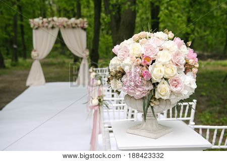 Beautiful bouquet of roses, peonies and tulips in stone vase in front of wedding arch