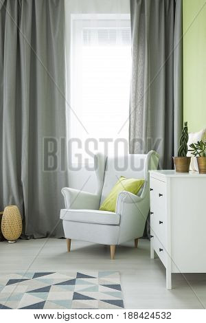 Room with grey armchair white dresser window curtain and plants