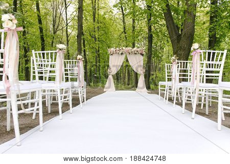 Beautiful wedding archway with lined up chairs with tenderless boutonnieres, outdoors