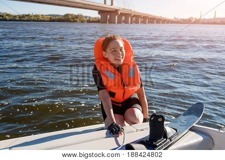 Young fit woman ready to ride water skis siting on the boat closeup. Athlete water skiing and having fun. Living a healthy lifestyle and staying active. Water sports theme.