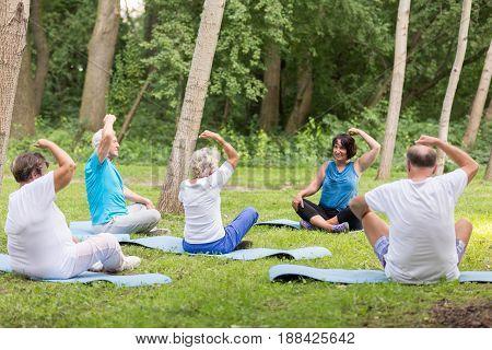 Active Grandparents Excercising In The Garden