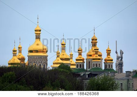 KIEV, UKRAINE - MAY 3, 2011: These are the domes of the church buildings of the Kiev-Pechersk Lavra and the monument of Motherland which is nearby.