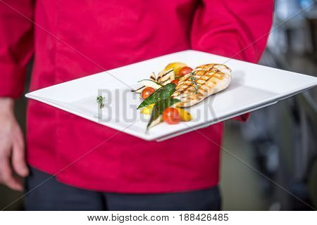 Chef in the hotel or restaurant kitchen is preparing meals. Chef with grilled chicken breast grilled vegetables on white plate. Professional chef with a portion of food.