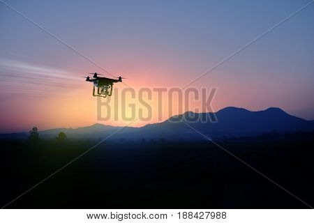 silhouette of drone flying to the mountain view at sunset with twilight sky.