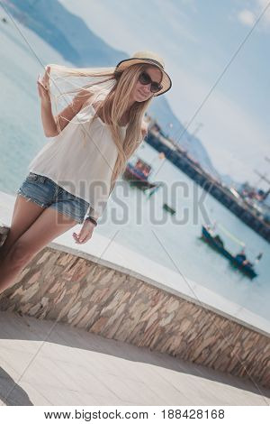 Beautiful woman standing on city embankment and enjoying the view, In a straw hat, with his back to the camera.