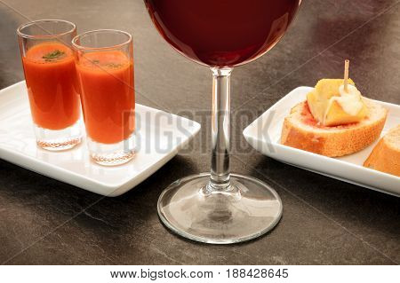 Spanish tapas in a modern bar. A glass of red wine, two shots of gazpacho, cold tomato soup, and pinchos of tortilla, Spanish omelette, on slices of bread. On a dark black table with a place for text