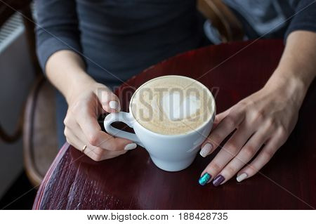 Hands Holding Cup Of Coffee With Foam And Heart