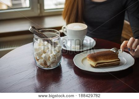 Jar Of Sugar, Cup Of Coffee With Foam And Tiramisu Cake On The Table