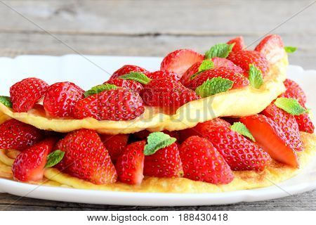 Diet filled omelette. Colorful omelette filled with fresh strawberries and garnished with mint on a plate and old wooden table. Breakfast omelette recipe. Closeup