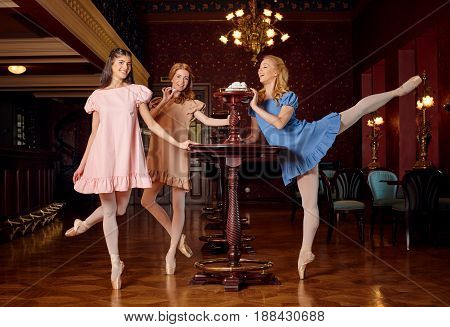 Young fashion ballerinas in colourful dresses want to taste a sweet meringue and zephyr