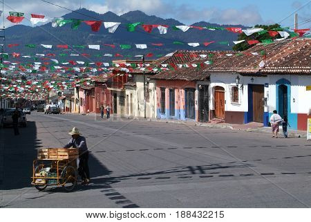 Cristobal de las Casas, Mexico - 19 January 2009: people walking on the street of San Cristobal de las Casas with numerous religious flags