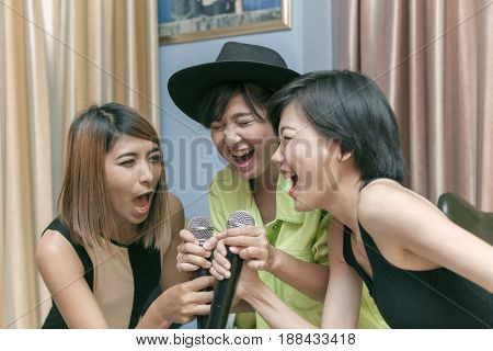 asian younger woman singing karaoke song with happiness face
