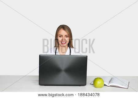 Young woman in white gown with stethoscope sitting at laptop with apple and book on table.