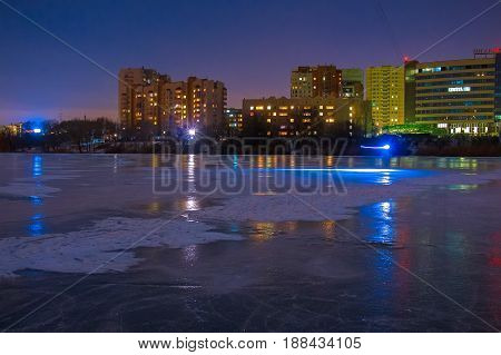 Beautiful night landscape of frozen river and city lights in background