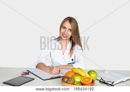 Young woman in white gown sitting at table with fruits and tablet writing in file on white.