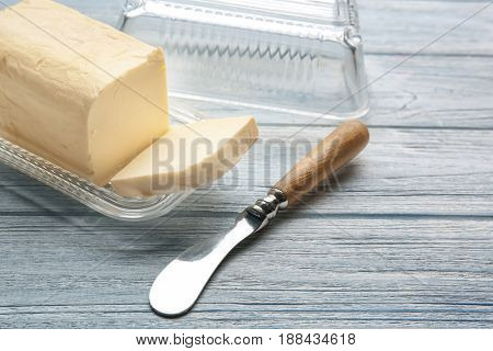 Dish with butter and knife on wooden table