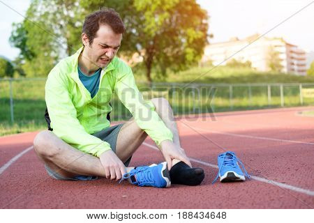 Running athlete feeling pain after an ankle injury