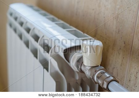 Close up white tap on modern radiator at home