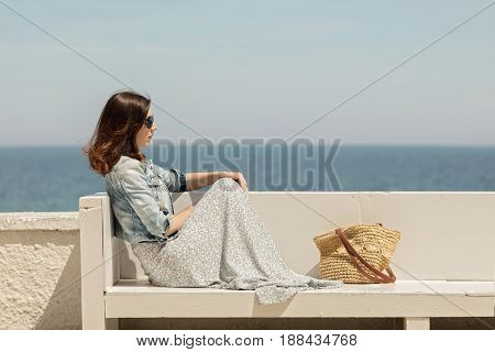 Young beautiful woman in a long skirt sits on a bench on a background of the sea horizon. Selective focus.