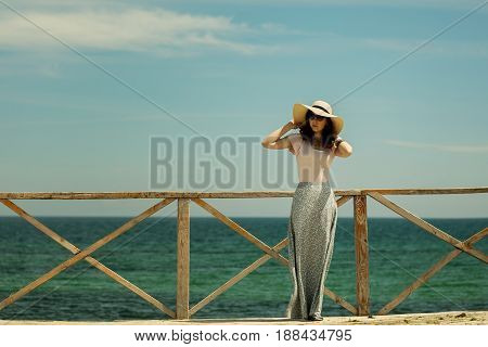 Young beautiful woman in a long skirt and hat stands on a wooden old pier on a background of a sea landscape. Selective focus.