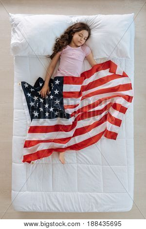 Young patriot. Nice pleasant young girl sleeping and having dreams about America while being covered with the US flag