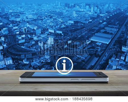 Information sign icon on modern smart phone screen on wooden table over city tower street and expressway Business communication concept
