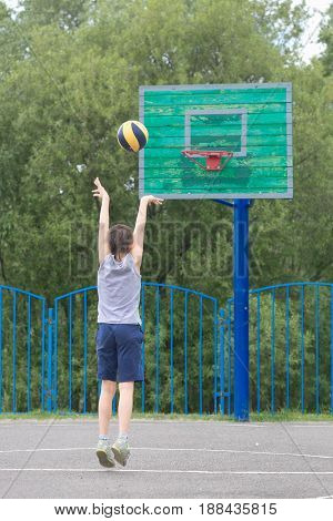 Teen In A T-shirt And Shorts Throws The Ball Into The Ring