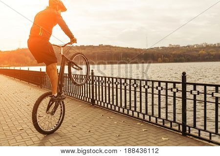 A biker performing the balance trick on the quay near the river. Horizontal outdoors shot.