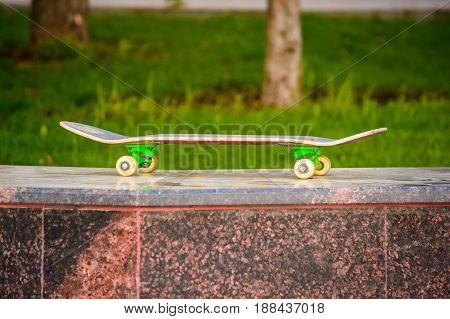 Closeup of a skateboard left on stone surface outdoors