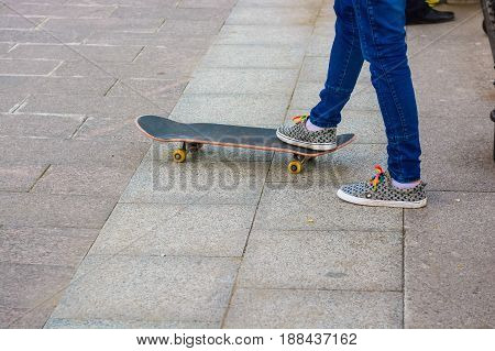 Lower part of teenage skater riding skateboard outdoors