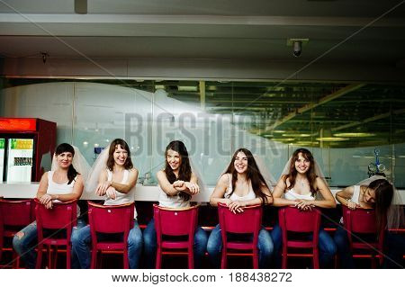 Six Girls On Veil Sit At The Bar Stools On Hen Party.