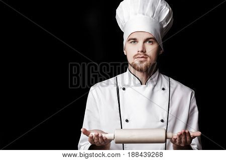 Young bearded man chef In white uniform holds a rolling pin on a black background