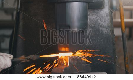 Automatic hammering - blacksmith forging red hot iron on anvil, extreme close-up, telephoto