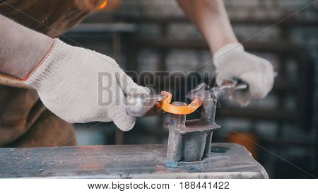 Close up view - hands of Blacksmith with gloves in forge makes steel knife, small business