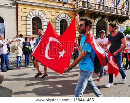 CLUJ-NAPOCA ROMANIA - MAY 27 2017: Turkish students holding the Turkish flag march on the streets at the opening parade of the Cluj Days festival.