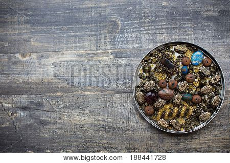 Small beads into tin lid on wooden background