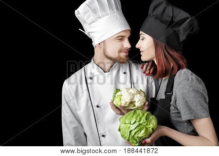 woman chef in black uniform and man chef In white uniform hold Fresh green cabbage and cauliflower on a black background