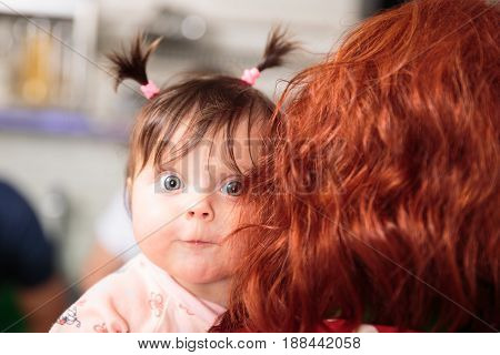 funny cute little girl surprised in the arms of mother