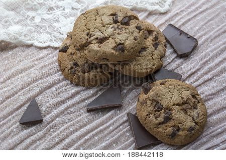 Four tasty cookies with dark chocolate on the light pink background