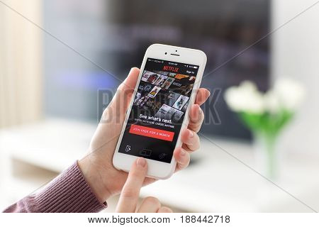 Alushta Russia - May 23 2017: Woman holding iPhone with app Netflix provides streaming media and video on the screen. iPhone was created and developed by the Apple inc.
