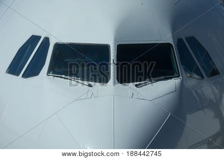 Close-up view of airplane nose and cockpit on airfield in airport.