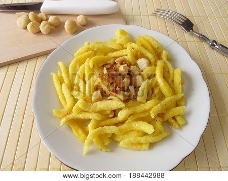 Sweetened spaetzle with roasted macadamia nuts on plate