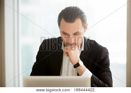 Serious businessman sitting in front of laptop and thinking about problem. Focused entrepreneur searching solution of difficult problem in internet. Man at computer ponders decision, working on report