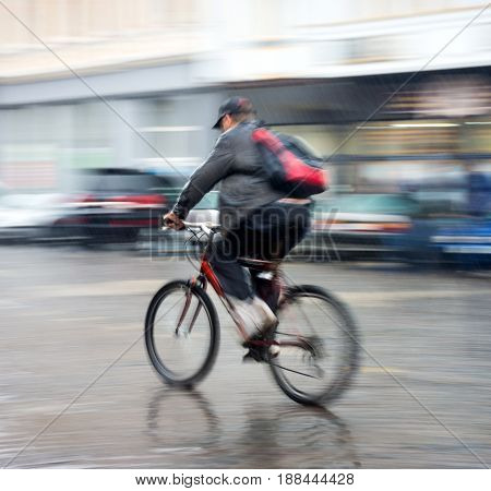 Cyclist On The City Roadway In A Rainy Day