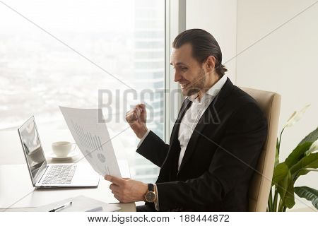 Successful businessman enjoys company fast grow, satisfied with financial results, profit increases. Excited guy at desk says yes when looking at graphs and charts document. Good business statistics